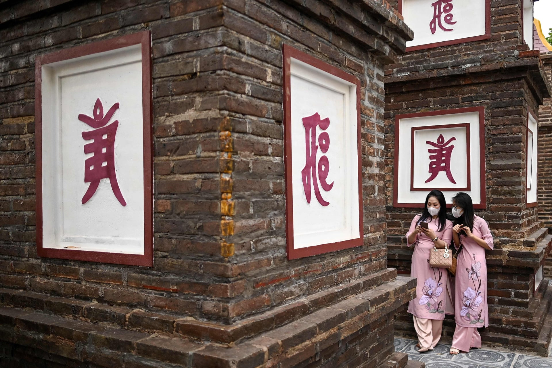 Two women check their smartphones at Tran Quoc Pagoda in Hanoi, 2021. Photo by AFP/Manan Vatsyayana.