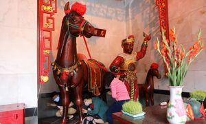 Crawling under a wooden horse for luck in Saigon pagoda