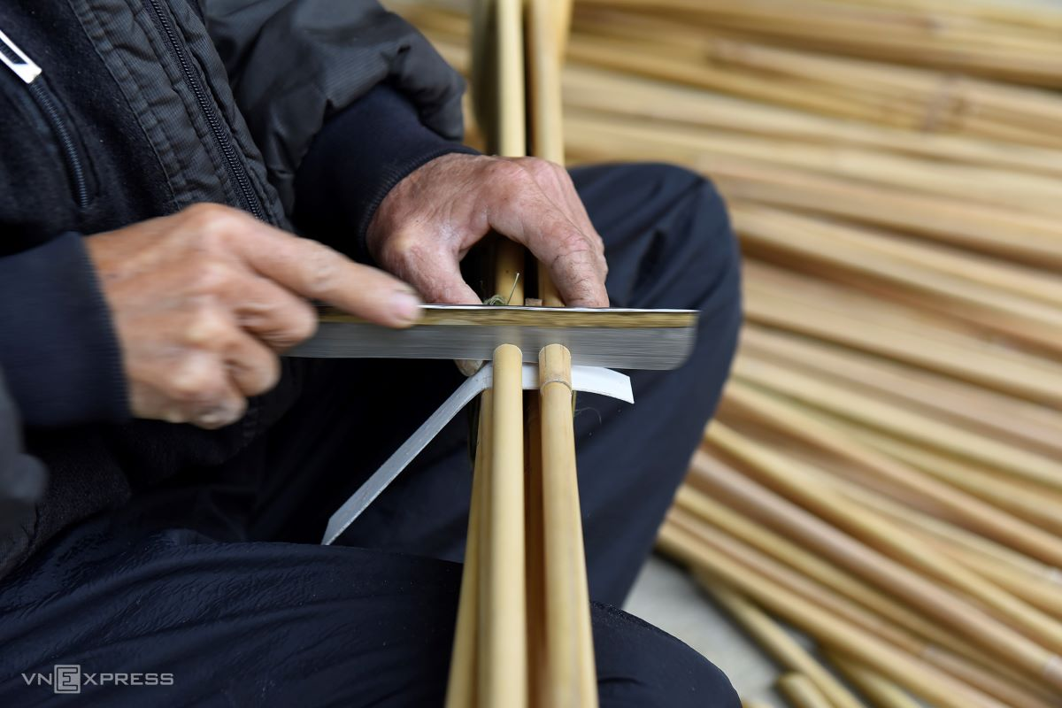 Tinh uses a small saw to cut the pipes one by one so their ends remain level.