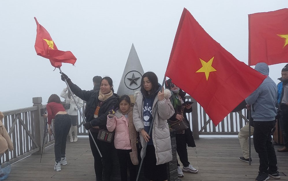 Tourists pose with national flags on top of Fansipan. Photo courtesy of Kiril Grudin.