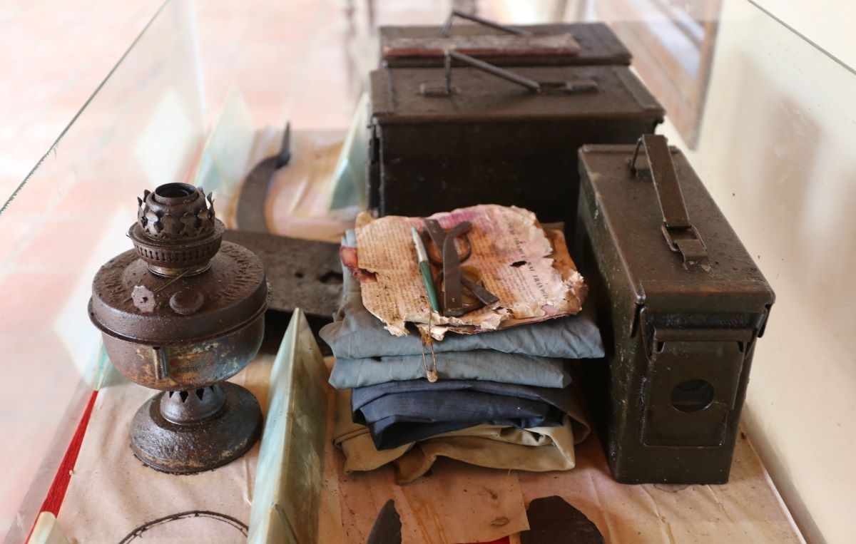 A collection of war memorabilia including clothes, a kerosene lamp and ammunition boxes.
