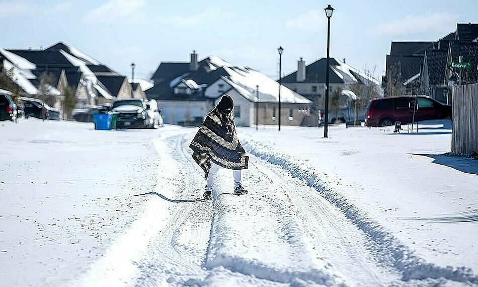 A man walks to his friends home in a neighborhood without electricity as snow covers Pflugerville, Texas, on Monday. Photo by Reuters.