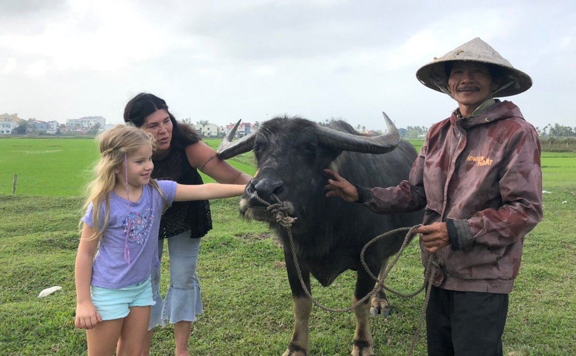 Rhon and her daughter gently touch the buffalo with dreamy eyes. Photo courtesy of Le Nhien.