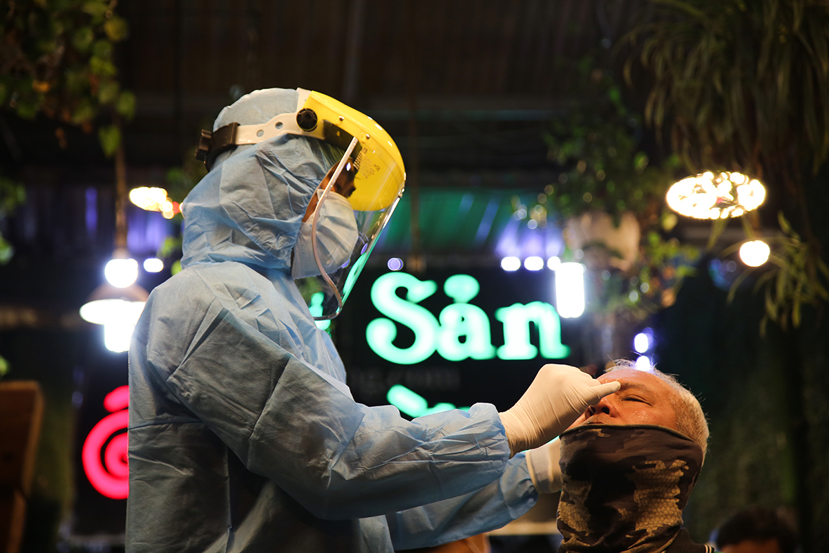 A medical staff takes nose swab from a man who dines at a restaurant in HCMCs Binh Thanh District February 22, 2021. Photo by VnExpress/Dinh Van