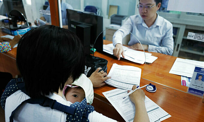 A mother takes her six-month-old daughter to the Hanoi Center for Employee Service in Cau Giay Districti to apply for unemployment benefits. Data from the center shows that of women account for 65 percent of people applying for unemployment benefits. Photo by VnExpress/Ngoc Thanh.