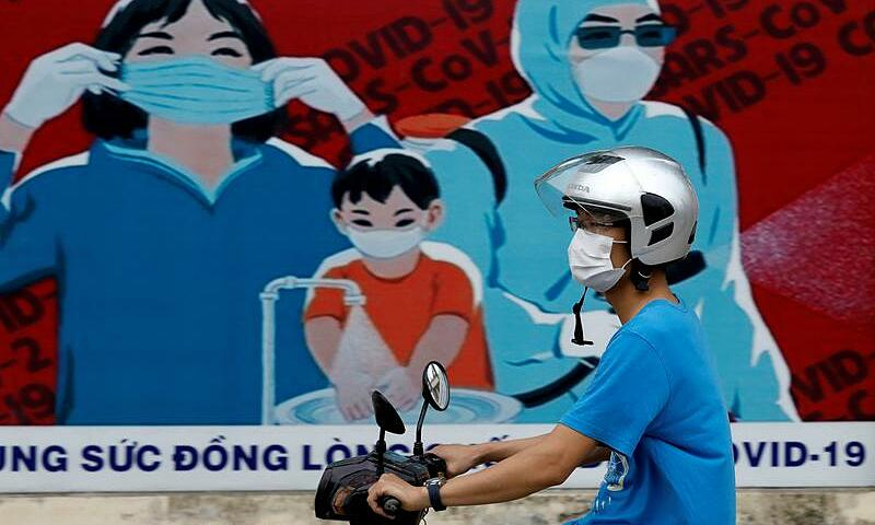 A man wears a protective mask as he drives past a banner promoting prevention against the Covid-19 pandemic in Hanoi, Vietnam July 31, 2020. Photo by Reuters/Kham.