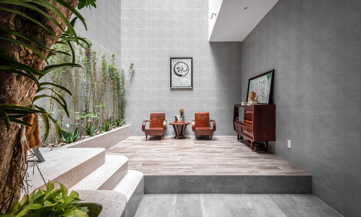 With no living room, homeowners put two chairs and a table on the ground floor to welcome their guests. Eliminating unnecessary spaces giving the house more space for trees and a swimming pool.