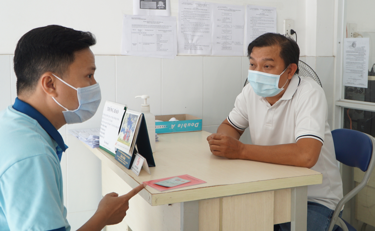 Phu (R) talks with a man asking for a certificate confirming he is not from a Covid-19 hotspot. Photo by VnExpress/Thu Anh.