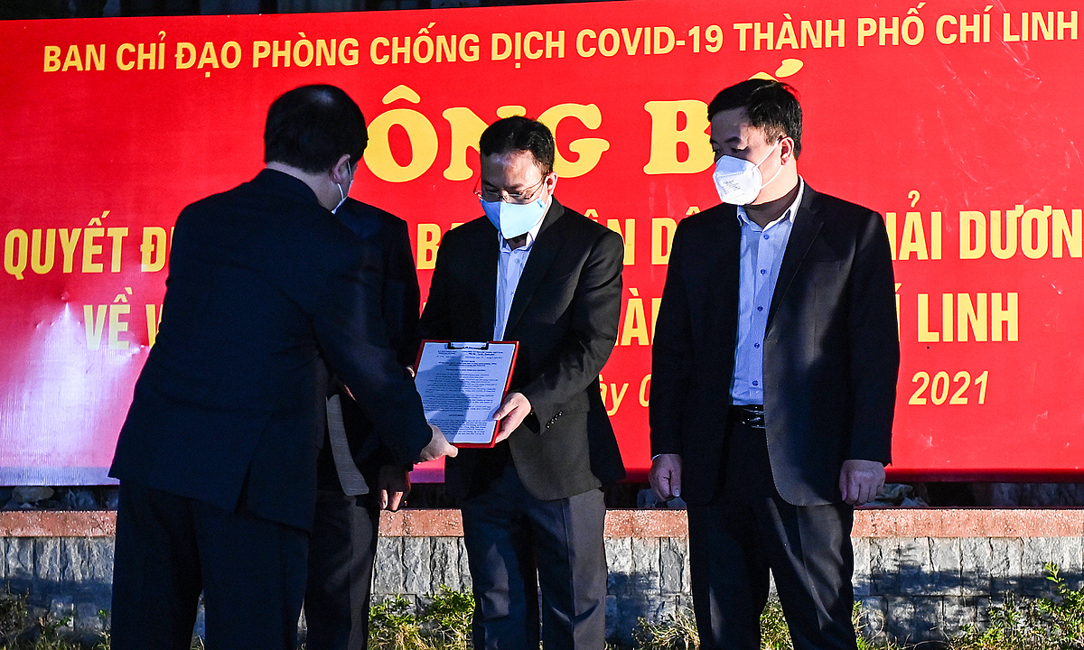 Nguyen Duong Thai, Chairman of Hai Duong Peoples Committee, hands the decision of halting the social distancing to leaders of Chi Linh Town.
