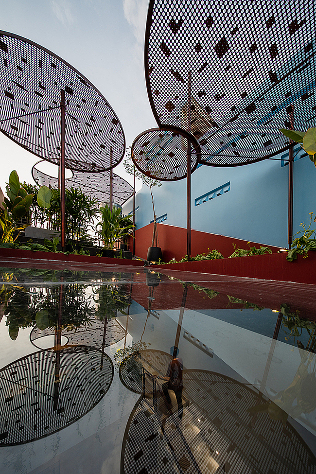 The sloped rooftop is utilized for growing shade plants, flowers, and organic vegetables. Steel umbrellas give the roof a distinctive look and reduce sunlight.