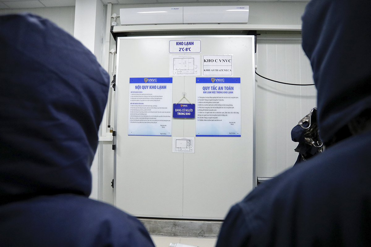 Two staff of the Vietnam Vaccine JSC (VNVC), importer of Covid-19 vaccines to Vietnam, stand outside a freezer where the vaccines are kept.  As required by the vaccine's developers, British-Swedish firm AstraZeneca and Oxford University, the doses are being kept at a temperature of minus 2-8 degrees Celcius.  VNVN had started work to make a freezer and super-cold storage in Ho Chi Minh City in October and November last year when Vietnam was still in the step of negotiating to buy the vaccine. Last Wednesday, 117,600 doses of AstraZeneca Covid-19 vaccine arrived in Ho Chi Minh City on a flight from Seoul. They are the first batch of 30 million doses Vietnam had ordered from AstraZeneca.