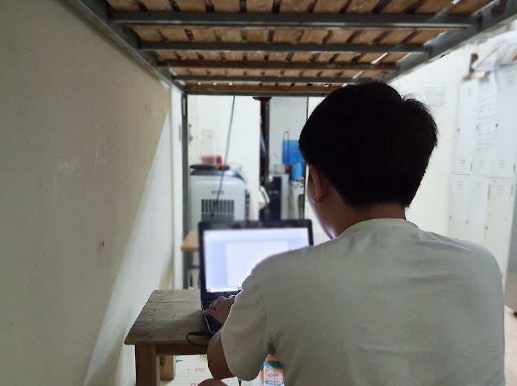 Hoang Minh doing data entry on his bunk bed in a boarding room in Hanois Cau Giay District. Photo courtesy of Minh.
