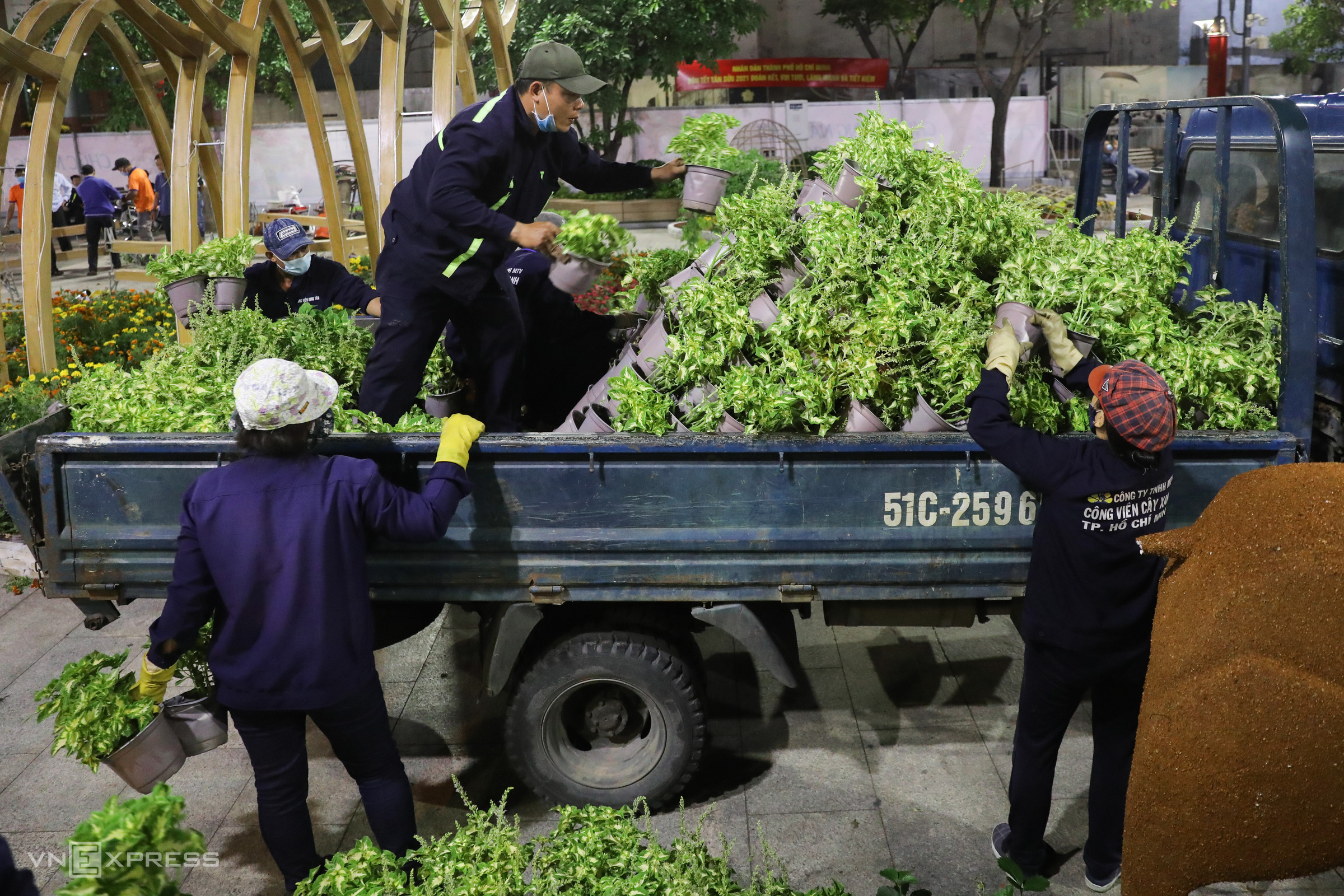 Sanitation workers classify flower pots. If those flowers are fresh, they will be stowed into trucks for reuse in parks and tourist areas.