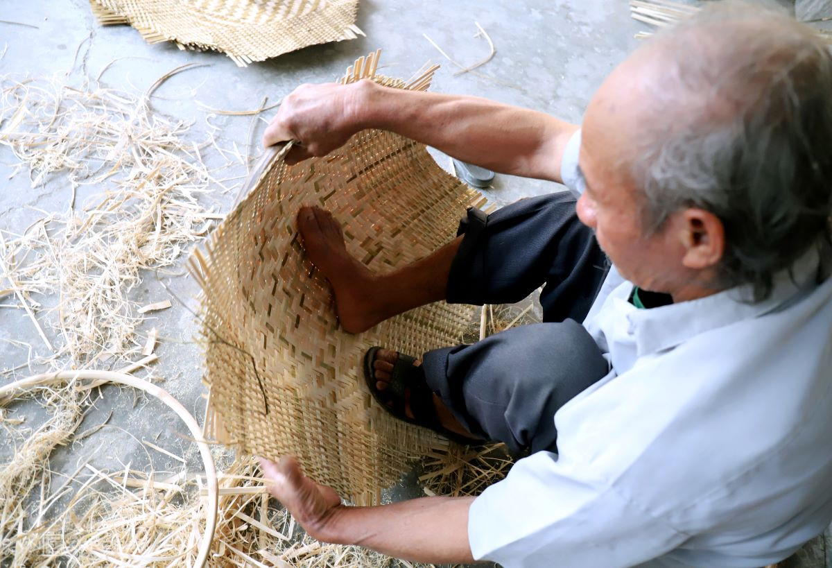 Son uses a leg to shape the mat, which is then fitted into a 70-centimeter diameter round frame.