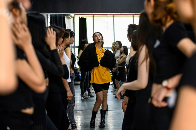 Instructor Pham Kieu Ly (center) demonstrates a pose to participants during a course teaching them how to pose for photographs on their mobile phones at a studio in Hanoi. Photo by AFP.