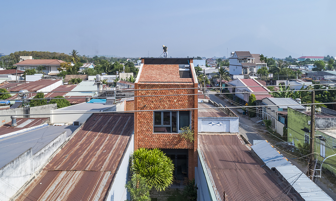 The two-floor house is located on a 175-meter-square plot. Covered by fish-scaled tiles, the house has a distinctive look in its neighborhood in southern Tay Ninh Provice.The tiles are kept by the family from their old dismantled house.