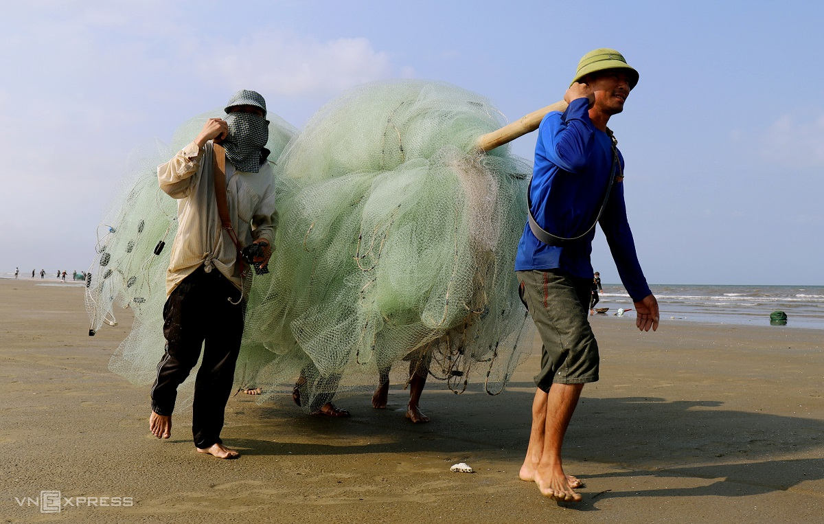 By the days end, fishermen carry their empty nets home to prepare for the next early morning catch of the day.