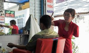 After losing arm, Vietnamese hairdresser styles new ways to cut clients' locks
