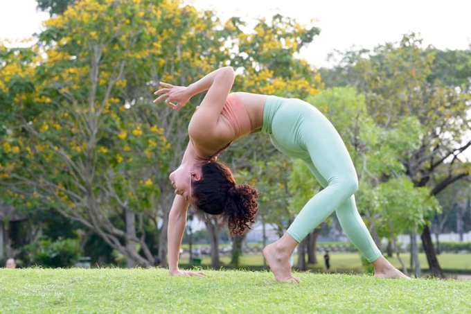 Xuan demonstrates a yoga pose to her students at a park in Hanoi. Photo courtesy of Xuan.