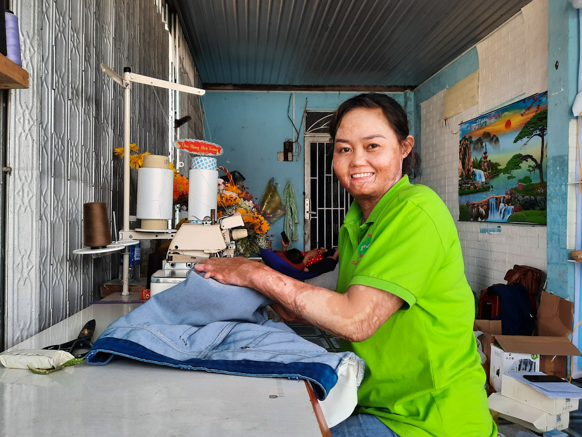Ngan sews clothes with her sewing machine. On the opening day of her store, some friends sent her flowers.