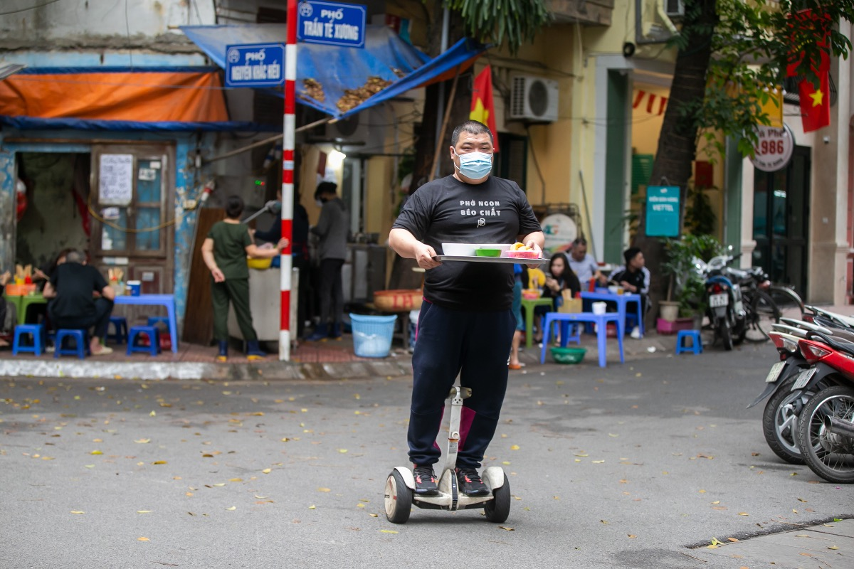A pho restaurant on Tran Te Xuong Street, Hanoi's Ba Dinh District, has caught public attention when its owner, Nguyen Thanh The, 43, uses a hoverboard to bring bowls of pho to his customers.
