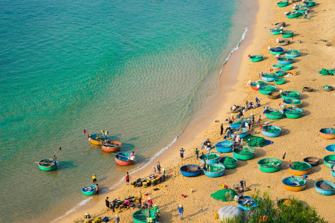 Coracleboats along Quy Nhon Beach in the central province o fBinh Dinh. Photo by Shutterstock/Huy Thoai.