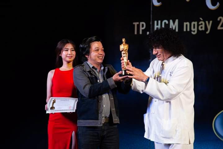 Tony Hassini, CEO of the International Magicians Society, hands over the Merlin Award 2019 to Ngo Duc Huy. Photo courtesy of Huy.