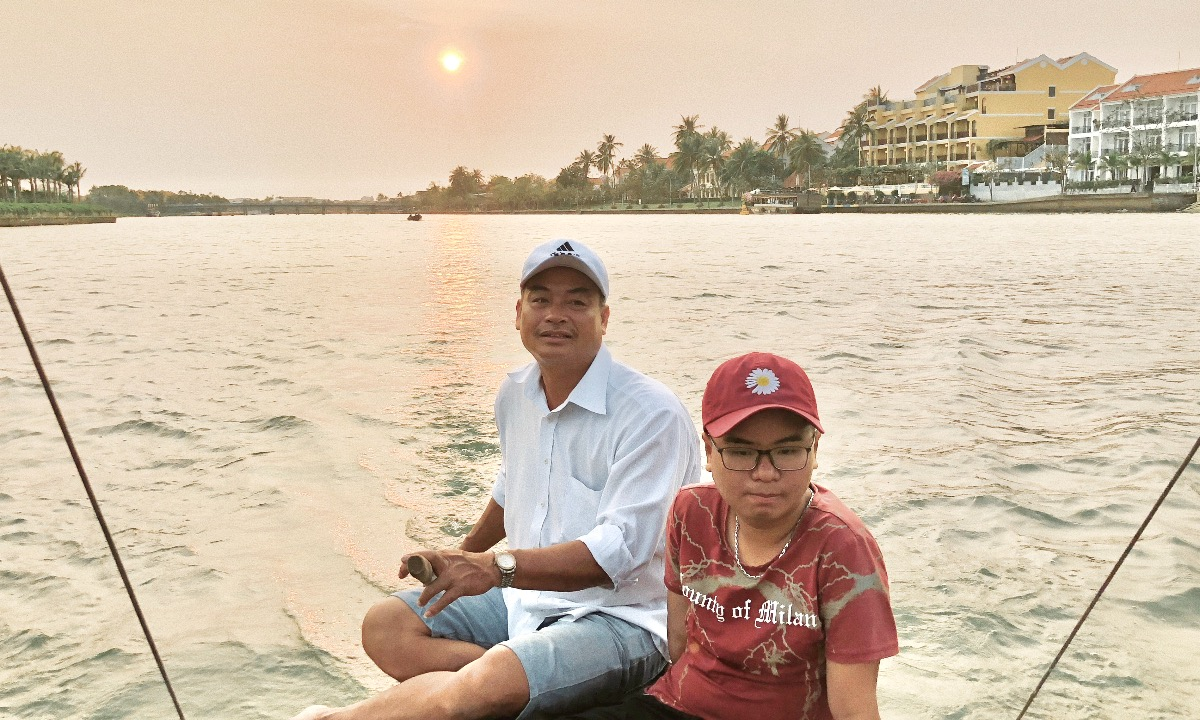 Boatman Truc (L) and his son have their first customer of the day on late Sunday, March 28, 2021. Photo by VnExpress/Long Nguyen.