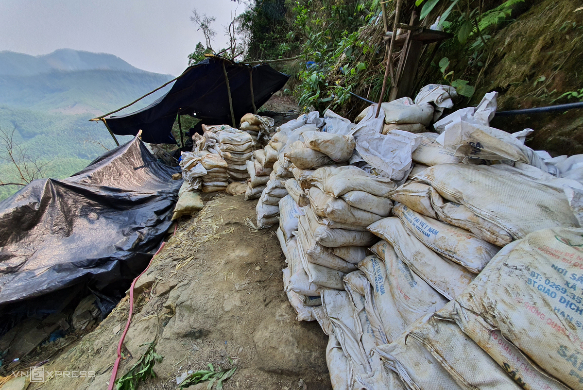 Tens of sacks containing gold ore are gathered on the cliffs, waiting to be transported by motorbike to chemical tanks to soak and filter gold.