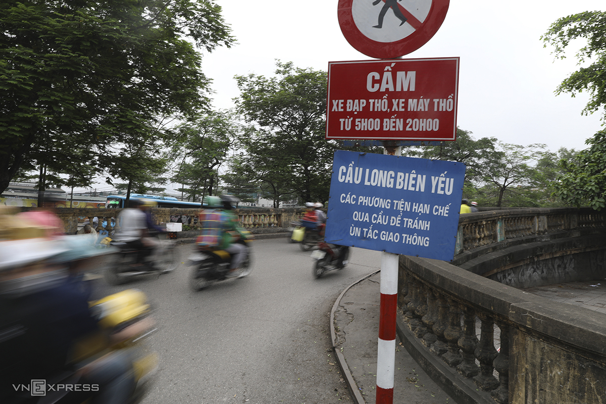 A signboard calls on vehicles to limit use of the bridge. However, due to urban developments along the banks of the Red River, thousands of motorbikes and bicycles cross the bridge during peak hours every day.