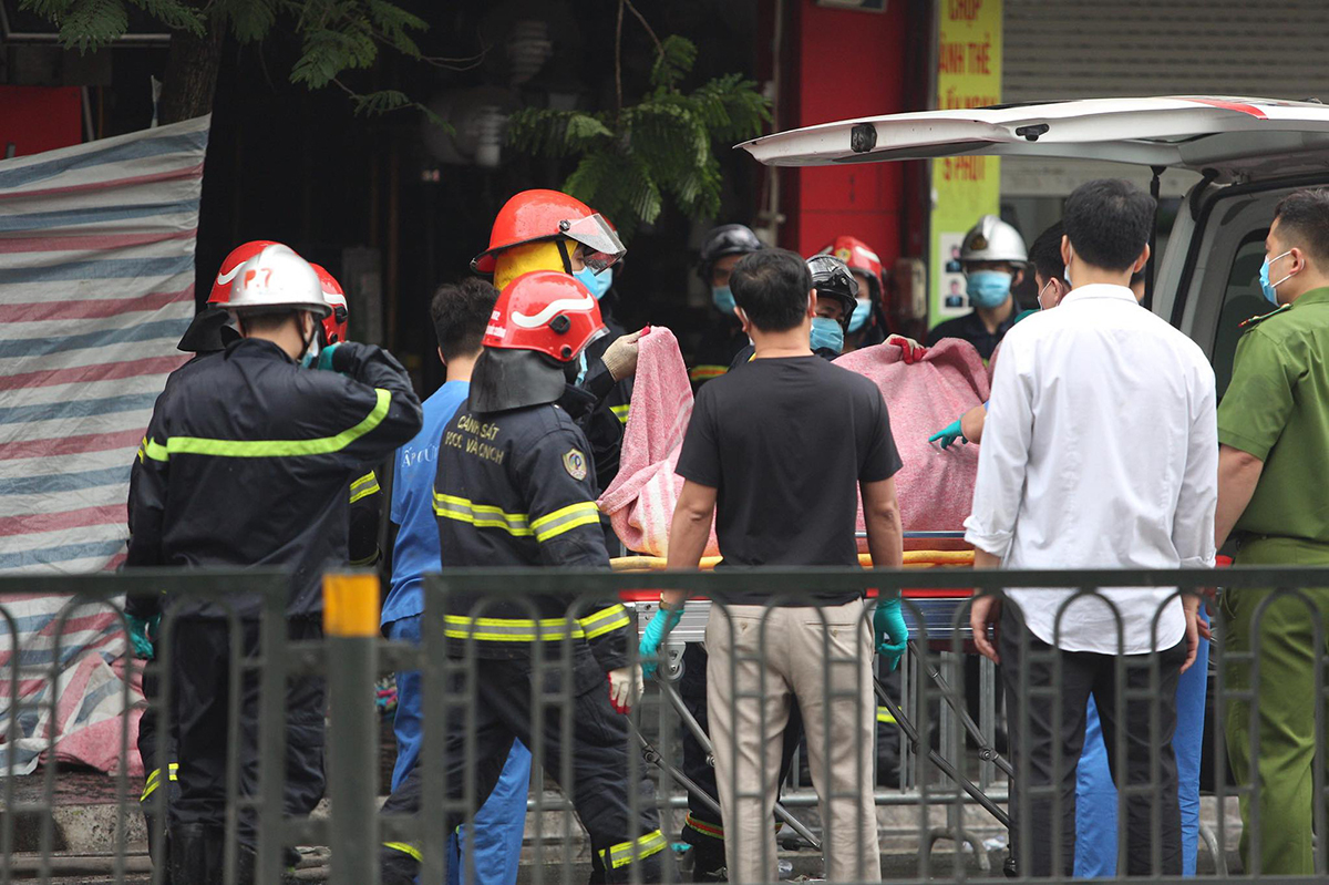 Firefighters bring the body of a victim out of the house in Dong Da District of Hanoi where a fire killed four family members on April 4, 2021. Photo by VnExpress/Nguyen Dinh