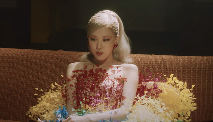 Rosé wears a high-low skirt decorated with dyed ostrich feathers by Cong Tri. Still cut from the video.