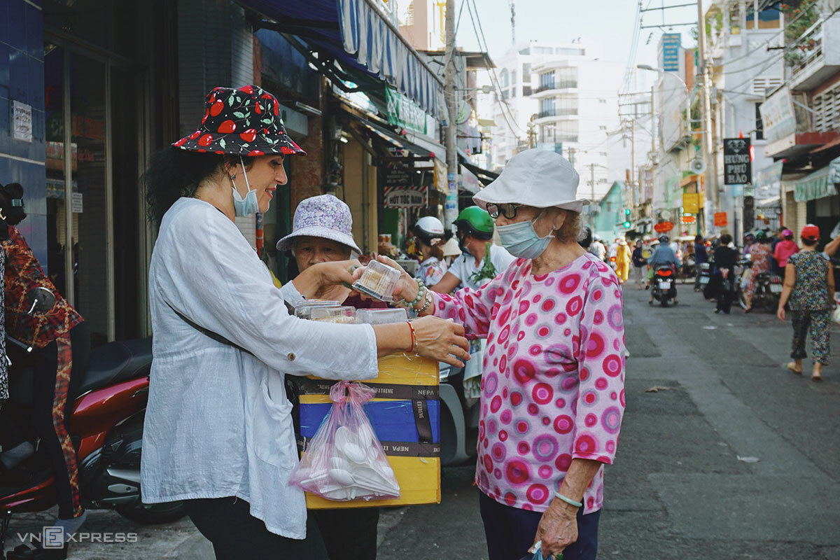 Irina (left) sells cakes outside Tan Dinh Market in HCM City.