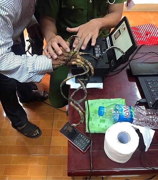 A policeman in Nam Dinh Province assists Luu Cong Huyen in getting fingerprints scanned. Photo acquired by VnExpress.