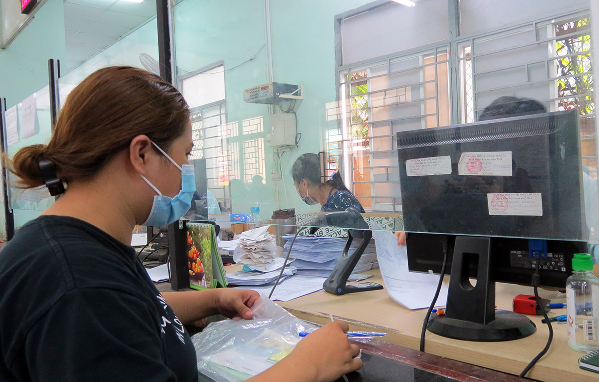 Vu Thanh Ha files documents to receive unemployment allowance at the Ho Chi Minh City Job Service Center. Photo by VnExpress/Le Tuyet.