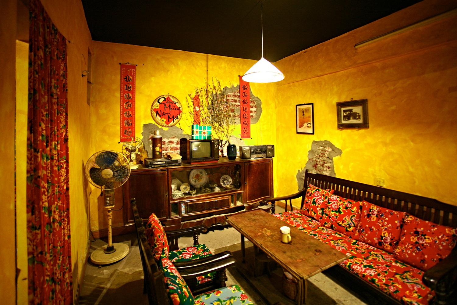 Even the lighting adds to the shop's subsidy era ambience. There is a space that is arranged just like a living room of that period, with a typical cupboard and a wooden salon set. Many decorations in the café are a throwback including peacock blanket covers, black and white TV, radio, thermos, and desk fans. Small peach branches and traditional square cake banh chung, and the Vietnamese distich evoke a traditional Tet atmosphere of those times.
