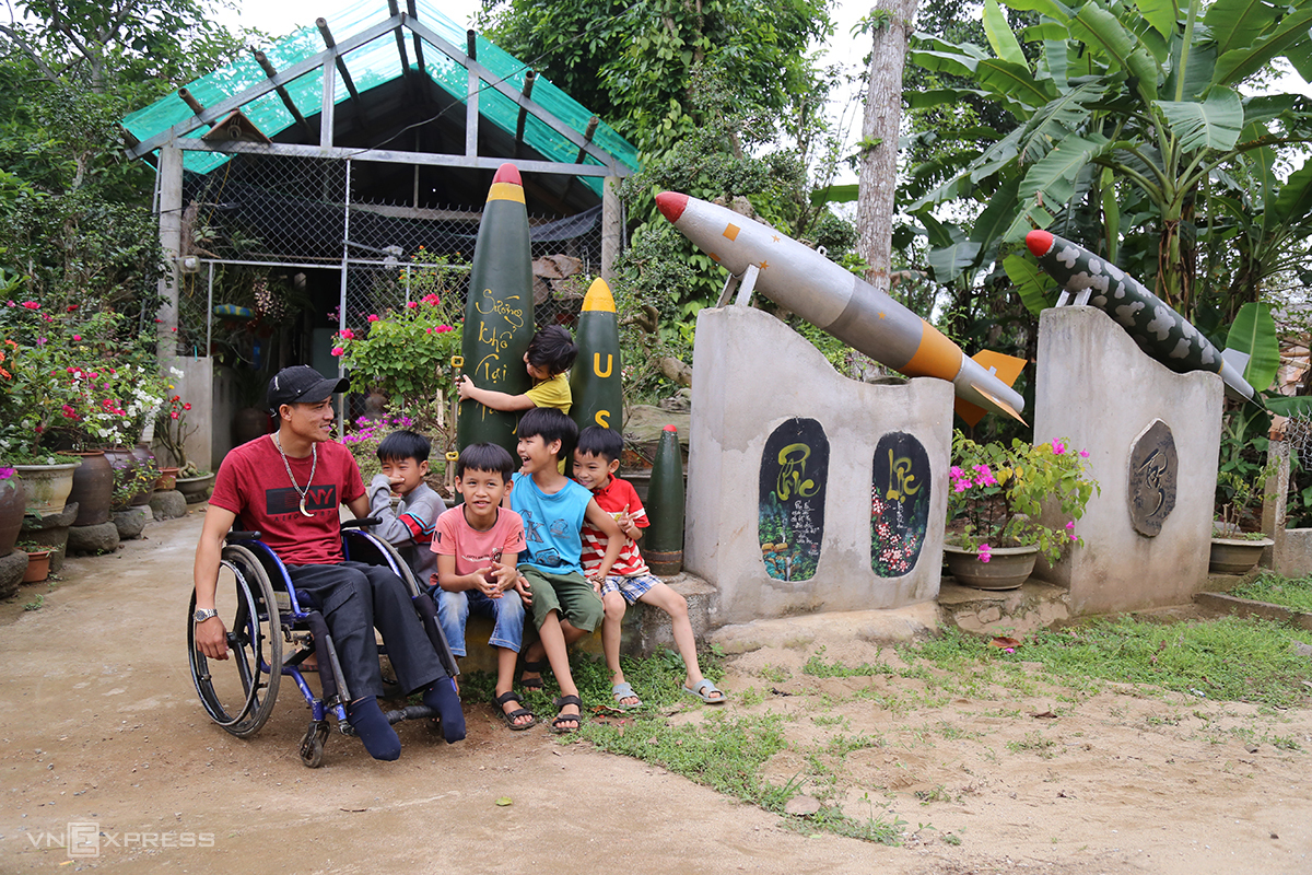 Le Van Hanh (L) pose with the neighborhoods children next to the bomb husks he collected. Photo by VnExpress/Hoang Tao.