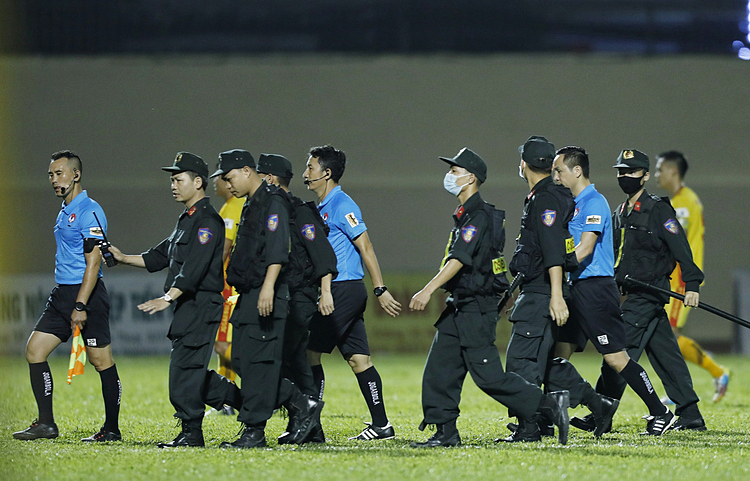 The mobile police officers escort the referees out of the stadium. Photo by VnExpress/Lam Thoa.