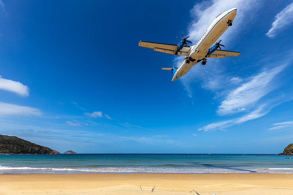 An aircraft flies close to Dam Trau Beach. Photo by Shutterstock/Tran Chi Thinh.