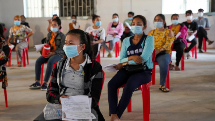 Garment factory workers and staff wait to receive Chinas Sinovac coronavirus vaccine at an industrial park in Phnom Penh, Cambodia, April 7, 2021. Photo by Reuters.