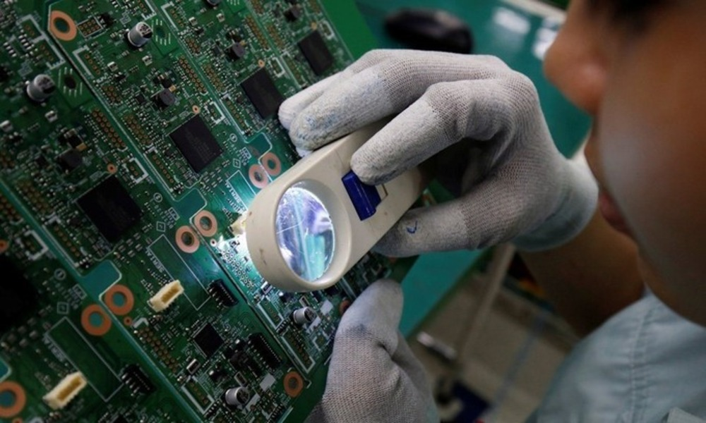 A worker looks through a magnifying glass to check errors of a printer circuit board at a factory in Bac Ninh Province. Photo by Reuters.