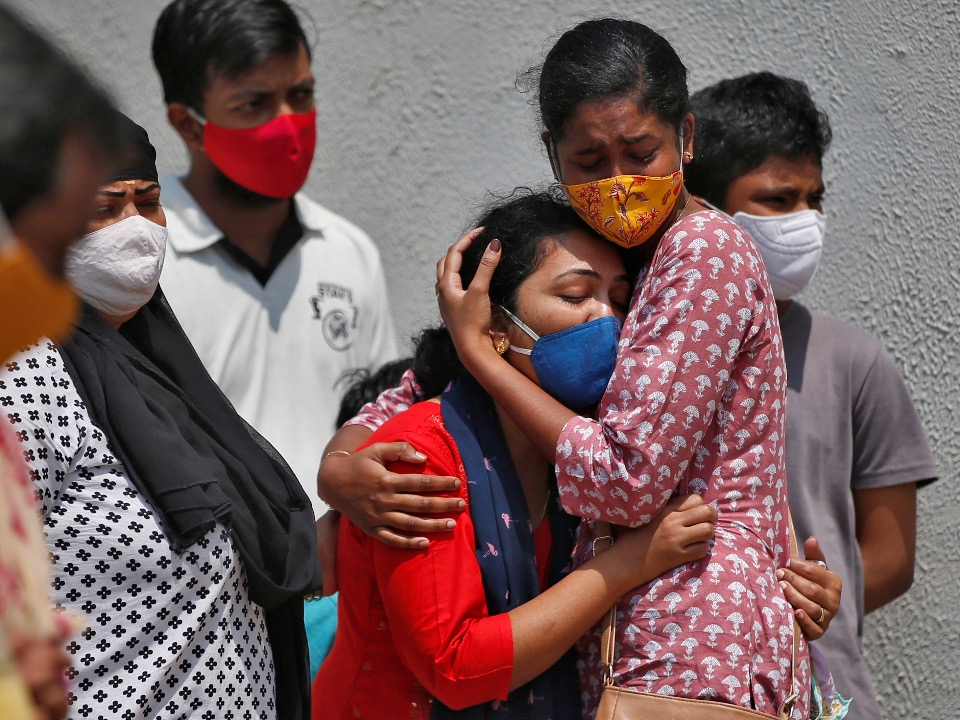 A woman is consoled after her husband died due to the coronavirus disease (Covid-19) outside a mortuary of a Covid-19 hospital in Ahmedabad, India, April 15, 2021. Photo by Reuters/Amit Dave.