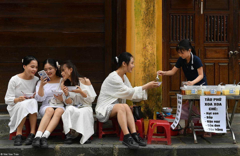 Girls eat che (sweet soup) on a street in Hoi An ancient town. Photo by Viet Van Tran.