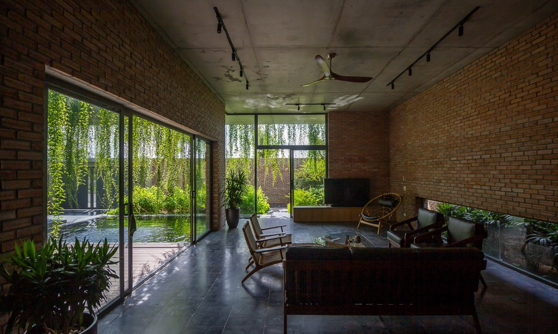 The main materials in the house are red bricks and bare concrete, creating a rustic feeling.