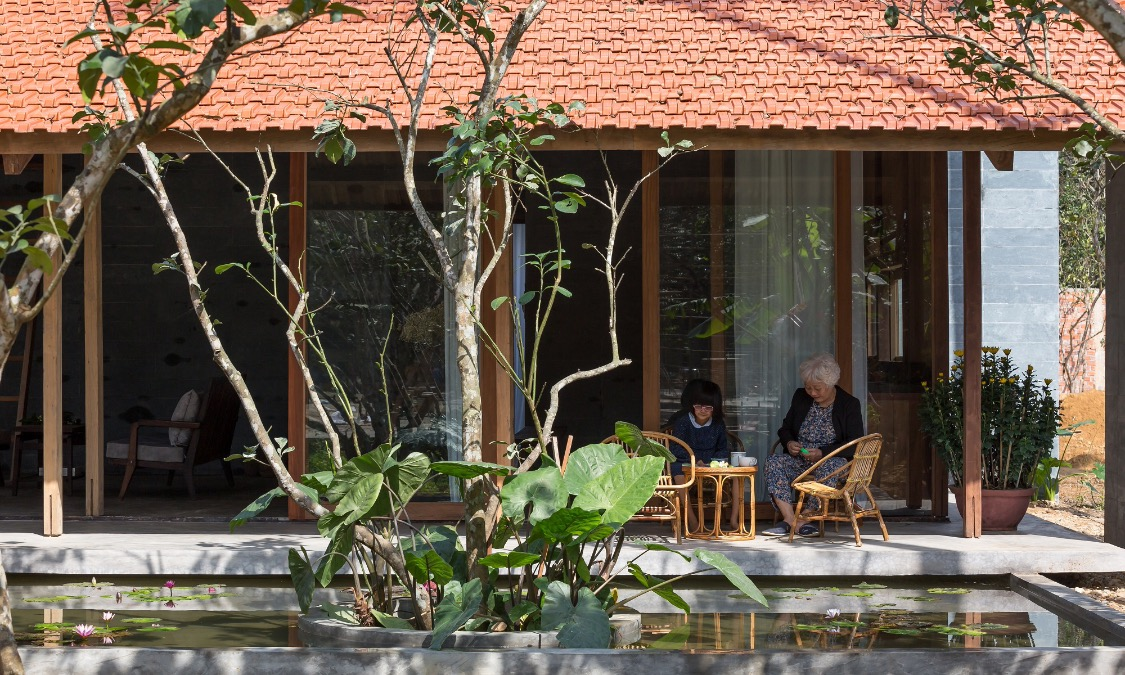 It is designed with a composition of a common area, two bedrooms, two restrooms, and their surrounding spaces. The common area including living, dining areas and kitchenette connecting with a veranda that goes along the main façade, facing a water lily pond in front of the house.