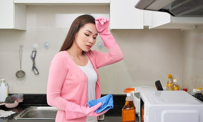 A tired woman cleans her kitchen. Photo by Shutterstock/Makistock.