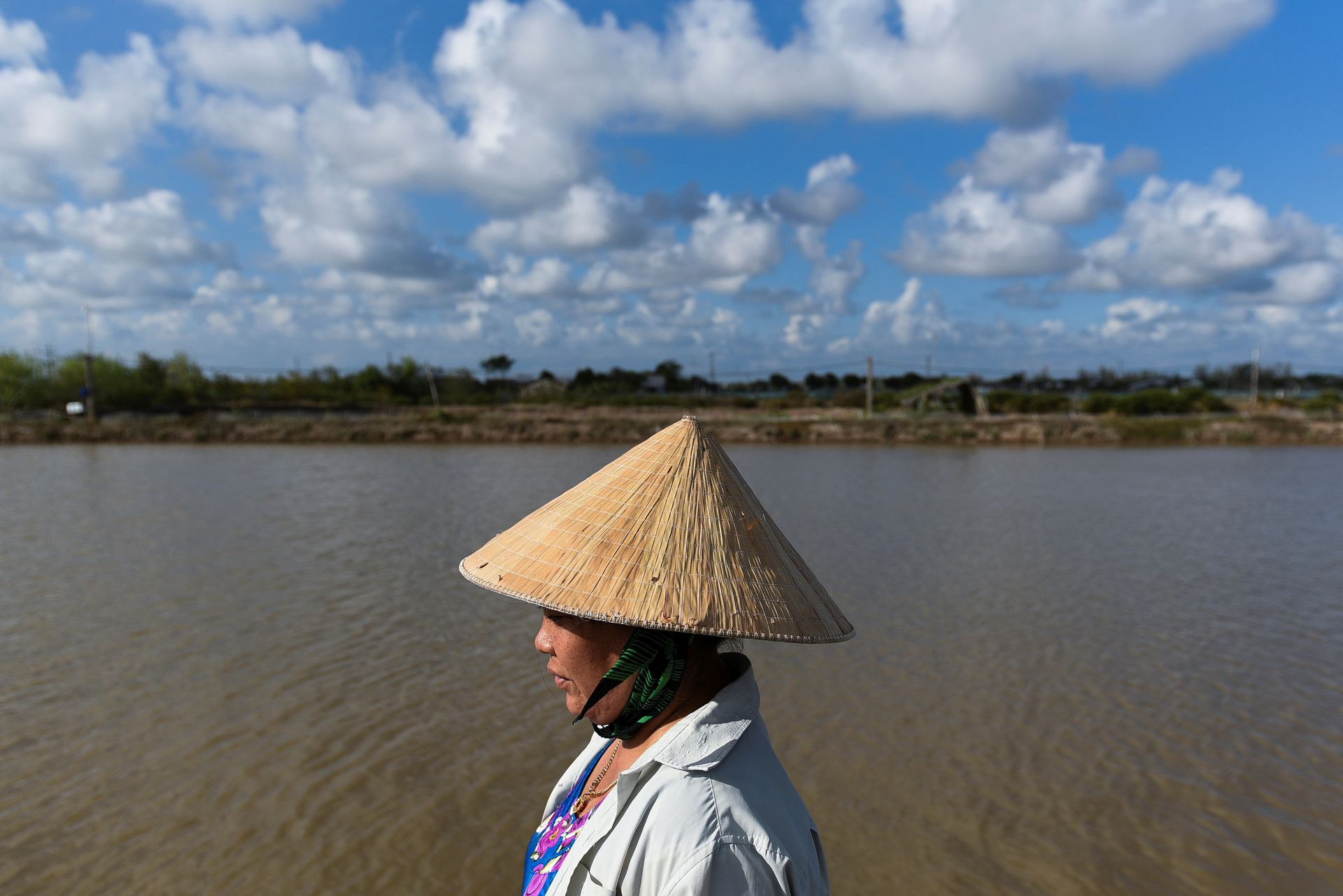 Ta Thi Thanh Thuy, 52, walks past the place where she used to grow rice before her family switched to shrimps farming in Soc Trang Province, Vietnam, May 1, 2021. Photo by Reuters/Thanh Hue.