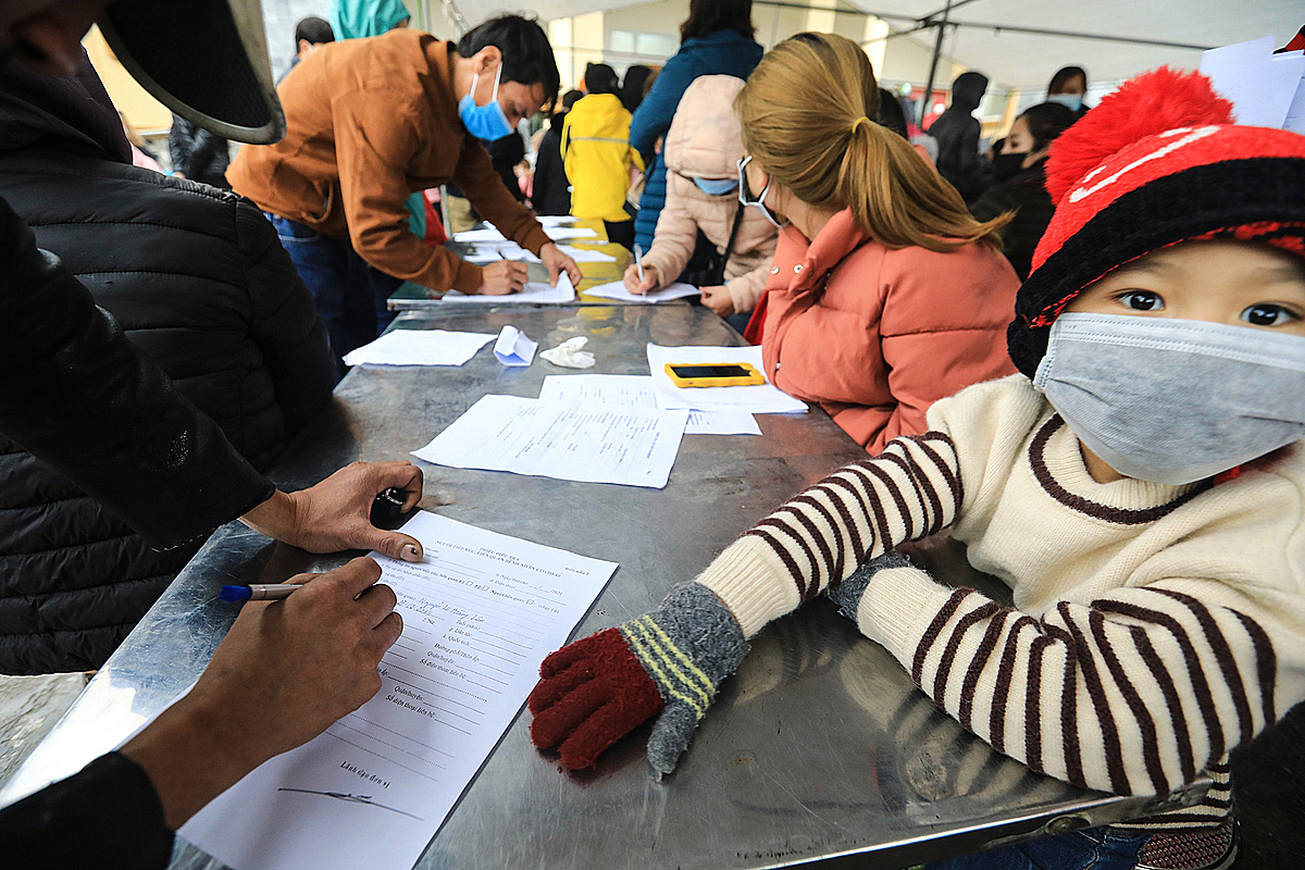 Parents fill out forms as teachers sort students into classes before Covid-19 sample collection, Hanoi, February 1, 2020. Photo by VnExpress/Giang Huy.