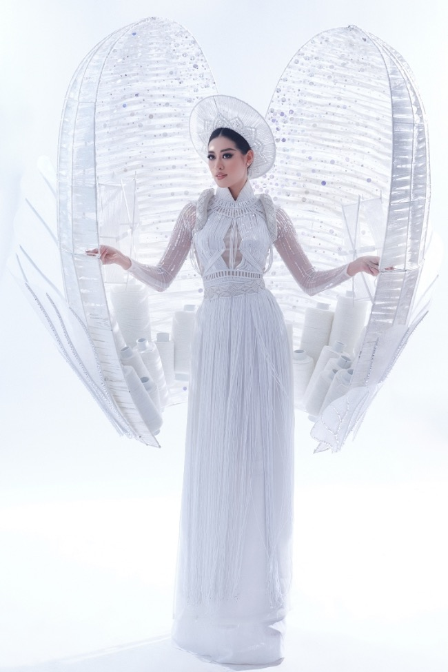 Khanh Van, Vietnamese contestant at Miss Universe 2020, dons a white ao dai with a 30-kg cocoon inspired by the image of the silkworm cocoon used in traditional silk weaving.Catriona Gray, Miss Universe 2018 winner, chose Khanh Van's cocoon as one of her favorite six outfits. She said: Indonesia, Nepal, Peru, Thailand, Ukraine and Vietnam were my Top 6 national costumes. Who were yours?The competition, planned to take place last year, was delayed until May, 2021. Photo by Milor Tran.