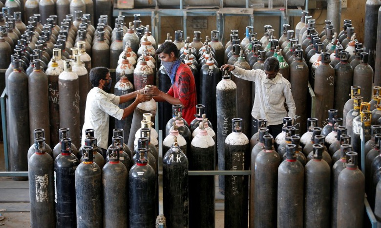 People carry oxygen cylinders after refilling them in a factory, amidst the spread of the Covid-19 in Ahmedabad, India, April 25, 2021. Photo by Reuters/Amit Dave.